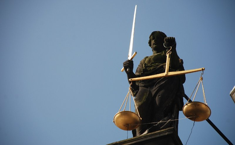 An image of a statue of Lady Justice on top of a court.